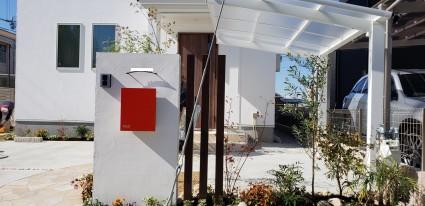 白壁と赤色ポストがオシャレな外構